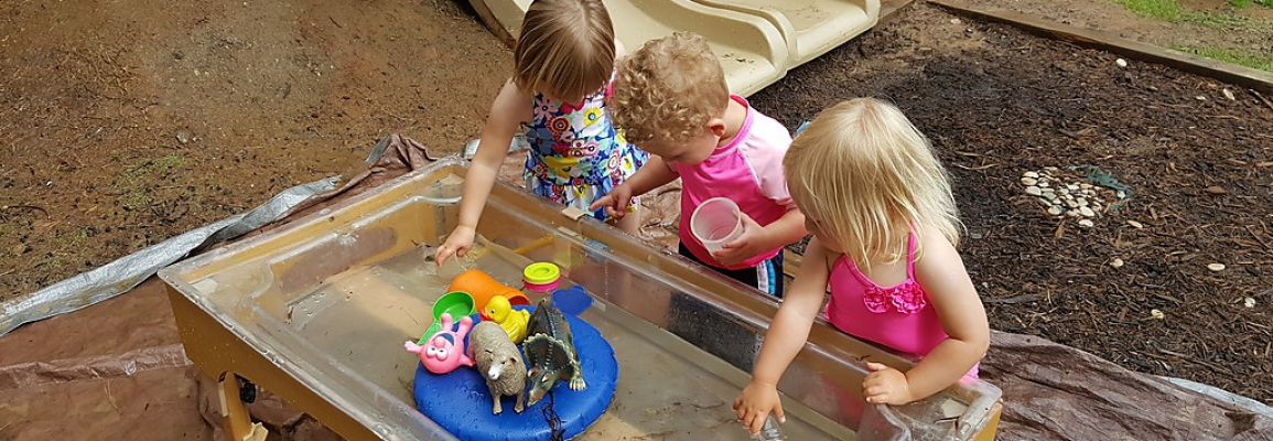 Toddlers playing in a water table with toys