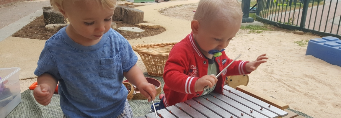 Toddlers playing with musical instrument