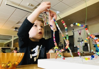 Toddler playing with beads