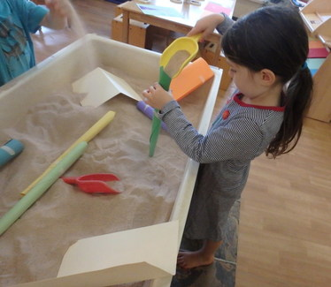 Preschool girl filling a paper made cone with sand using a shovel